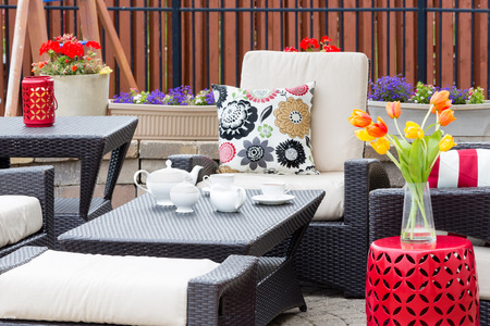 seating furniture: Tea served on an outdoor patio between flowers in flowerpots and tulips in a vase with comfortable armchairs and cushions for a relaxing break