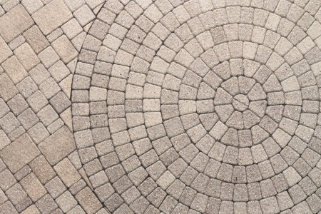 Paver bricks arranged in a circular pattern of concentric geometric circles. Architectural background of an ornamental pattern in outdoor patio paving. Stockfoto