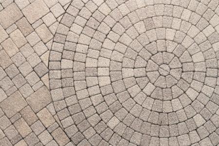 empedrado: Pavimentadora ladrillos dispuestos en un patrón circular de círculos concéntricos. Geométricas Fondo arquitectónico de un patrón ornamental en la pavimentación del patio al aire libre.