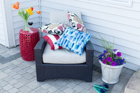 Pile of colorful cushions on a comfortable outdoor armchair flanked with fresh spring tulips and flowers for a relaxing place to enjoy a shady break on a hot day Фото со стока