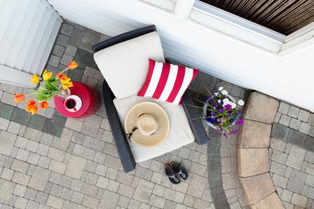 深い座席パティオでリラックスできるお茶休憩を取って快適な肘掛け椅子の sunhat のカラフルな春の花が並ぶし、レンガの庭の靴舗装された屋外パテ 写真素材