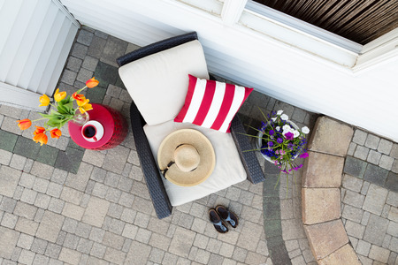 Taking a relaxing tea break in a deep seating patio set with a comfortable armchair flanked by colorful spring flowers with a sunhat and garden shoes on a brick paved outdoor patio, overhead view Stock Photo