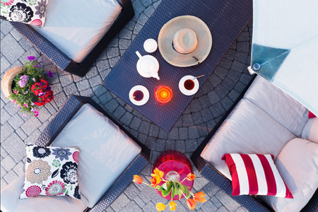 Relaxing evening on the patio having tea by candlelight with comfortable deep seating armchairs and colorful flowers around a table set with tea and a straw sunhat, overhead view