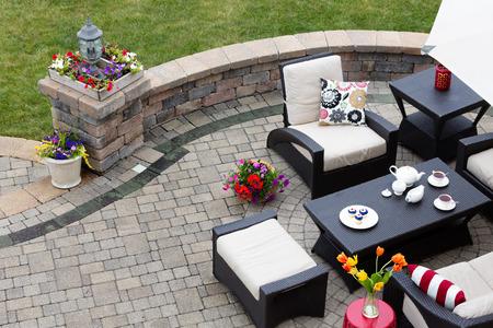 レンガ舗装モダンなアームチェアの快適なテラスの家具が付いているテラスやテーブルの周り便は茶と緑の芝生、高角度のビューを見下ろす低いカ 写真素材