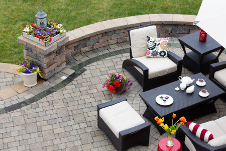 Brick paved patio with comfortable patio furniture with modern armchairs and a stool around a table set with tea and cookies alongside a low curving wall overlooking a green lawn, high angle view Archivio Fotografico