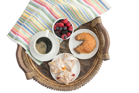 pastries: Tasty morning breakfast on a wicker tray with freshly baked pastries filled with cheese, strawberry and peach, a croissant with chocolate hazelnut spread, coffee and fresh berries, overhead on white Stock Photo
