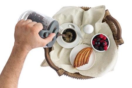 energising: Overhead view of the hand of a man pouring himself fresh breakfast coffee in a cup on a breakfast tray with fresh berries, a pastry and boiled egg, isolated on white