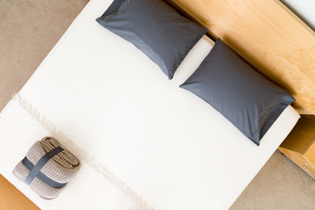 Overhead view of a neat king size bed in a hotel or house with black pillows on a white counterpane with a folded and strapped rug at the food and a wooden headboard
