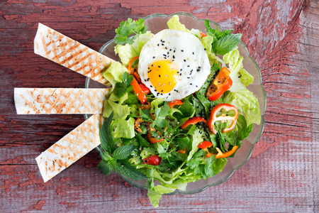 Fresh leafy green mixed salad with lettuce and herbs, tomato and sweet bell peppers served with a seasoned fried egg and wafers, viewed from above on a rustic wooden table Stock Photo