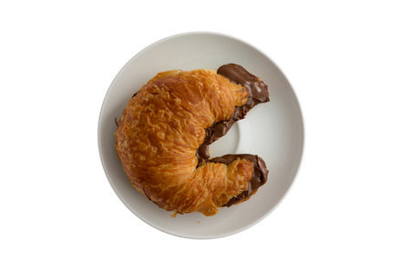 Freshly baked flaky buttery croissant filled to overflowing with hazelnut chocolate spread oozing onto the plate, tempting breakfast viewed from overhead isolated on white Фото со стока - 41261114