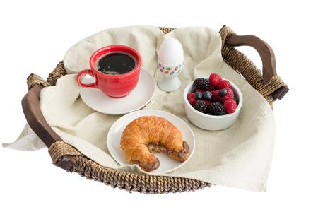 白い背景の上 - 食欲をそそる朝食トレイ - ゆで卵、ブラック コーヒー、ミックスベリーとヘーゼル ナッツのクロワッサンのボウルの高角度のビュー