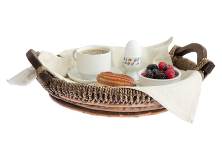 low  angle: Rustic wickerwork breakfast tray set with coffee, egg, pastry and fresh assorted berries viewed low angle isolated on white Stock Photo