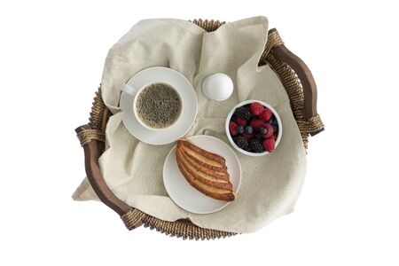 Tasty breakfast for one on a rustic wicker tray with a cup of fresh espresso coffee, boiled egg, ramekin of fresh assorted berries and a crispy pastry viewed from above isolated on white