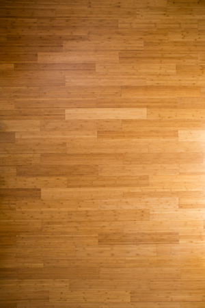 side lighting: Background texture of a wooden bamboo floor with laminated floorboards, viewed overhead with side lighting and a gradient for an architectural or interior decor theme