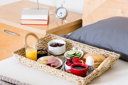 bedside: Close Up of Breakfast Tray Filled with Variety of Foods Sitting on Unmade Bed Next to Bedside Table with Lamp and Alarm Clock in Hotel Room Stock Photo