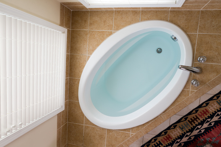 Modern oval domestic bathtub full of clean water in a brown tile surround below a tall window with blinds viewed from above 写真素材