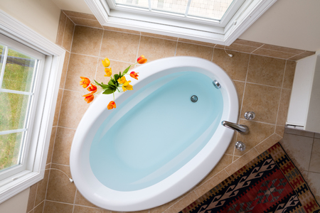 flanked: Corner oval bathtub full of clean water sunken into a brown tile surround and flanked by two tall view windows, overhead view