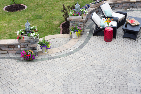 backyard: Decorative brick paving on an outdoor patio with a circular pattern and curved steps flanked by spring flowers leading to a green lawn, comfortable seating in the background