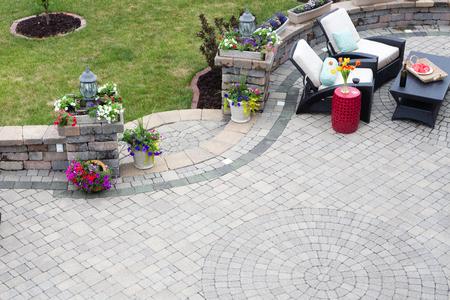 Pavimentación de ladrillo decorativo en un patio al aire libre con un patrón circular y pasos curvos flanqueados por flores de primavera que conducen a un césped verde, asientos cómodos en el fondo