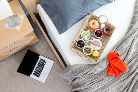 Erhöhte Ansicht des Frühstückstablett auf Ungemachtes Bett im Hotelzimmer in Geschäftsreise-Konzept-Bild mit Open Laptop auf dem Boden