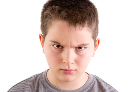 Head and Shoulders Close Up Portrait of Young Boy Looking at Camera with Stern and Disapproving Expression and Furrowed Brow in front of White Background