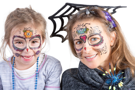 Pretty woman and her cute young daughter in Halloween makeup wearing a spider and its web looking at the camera with happy playful smiles, head and shoulders portrait over white Imagens