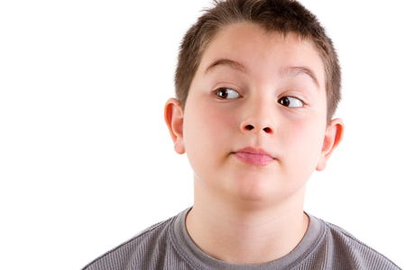 sideways glance: Head and Shoulders Close Up Portrait of Young Boy Looking to the Side with Curious Expression in front of White Background with Copy Space