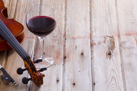 Pair of Violin Instrument and Glass of Wine Wine on a Wooden Floor with Copy Space on the Right.