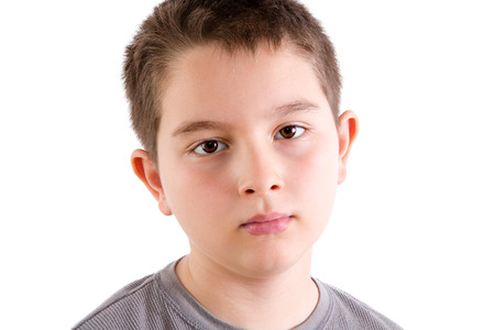 blank expression: Head and Shoulders Close Up Portrait of Young Boy in Gray T-Shirt Staring at Camera with Blank Expression in Studio with White Background
