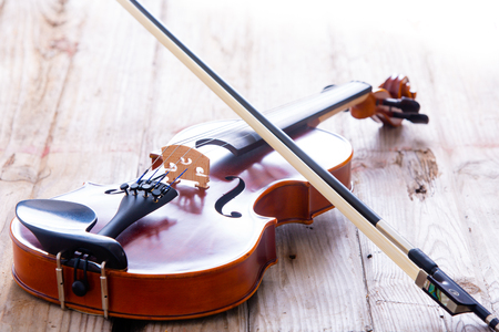 Close up Small Violin Musical Instrument for Kids Resting on a Wooden Floor. Stock Photo
