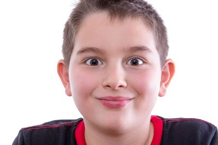 closed mouth: Head and Shoulders Close Up Portrait of Young Boy Wearing Black and Red Shirt Looking at Camera with Wide Eyes and Closed Mouth Smile in Studio on White Background Stock Photo