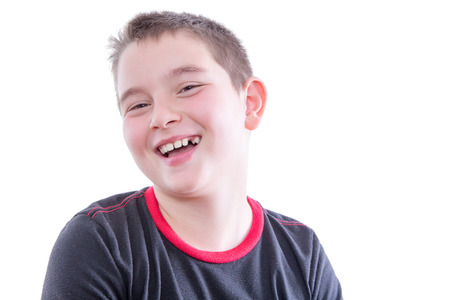exuberant: Head and Shoulders Close Up Portrait of Young Boy Wearing Black and Red Shirt Laughing and Showing Braces in Bright Studio with White Background and Copy Space