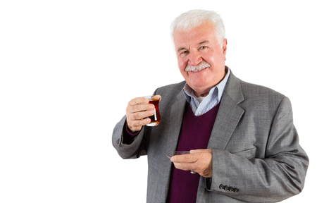 Half Body Shot of a Senior Businessman Holding a Glass of Turkish Tea and Smiling at the Camera Against White Background. Stock Photo