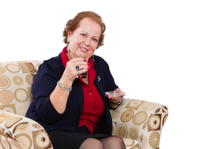 partake: Senior Businesswoman at her Seat Inviting to Have a Tea with a Smiling Face, Isolated on White Background. Stock Photo