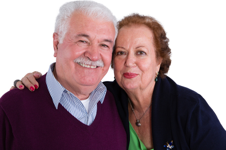 inseparable: Happy loving senior couple posing in a close embrace smiling happily at the camera, head and shoulders portrait isolated on white Stock Photo