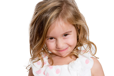 shyness: Close up Charming Blond Little Girl Smiling to You Shyly Against White Background. Stock Photo