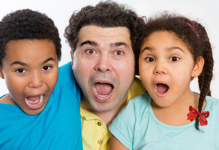 astounded: Close up Surprised Dad with Two Cute Kids Looking at the Camera with Mouth Wide Open Against White Background, Emphasizing Multicultural Family. Stock Photo