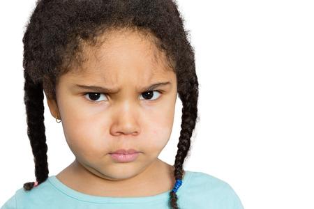Zblízka mladá dívka zírá na vás s Rozhněvaný výrazu obličeje proti bílému pozadí.