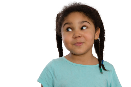 speculative: Charismatic little African American girl looking sideways with a cute knowing smile and speculative look, head and shoulders isolated on white with lateral copyspace Stock Photo