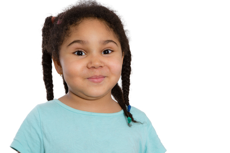 impish: Cute little African American girl with her curly hair in braids looking at the camera with a sweet impish smile, head and shoulders on white with copyspace