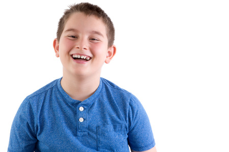 mirth: Carefree attractive young boy enjoying a good joke standing laughing at the camera, head and shoulders portrait isolated on white with copyspace Stock Photo