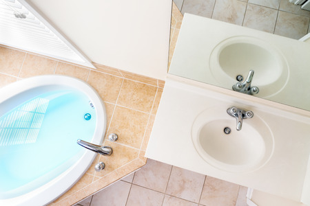 corner tub: Interior architecture of full bathtub and acrylic sink with faucets Stock Photo