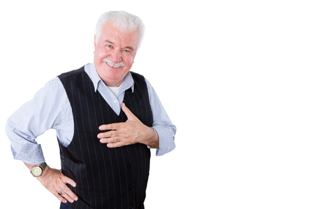 gracious: Gracious polite elderly man showing his gratitude and thanks holding his hand to his heart and looking at the camera with a beaming smile, isolated on white Stock Photo