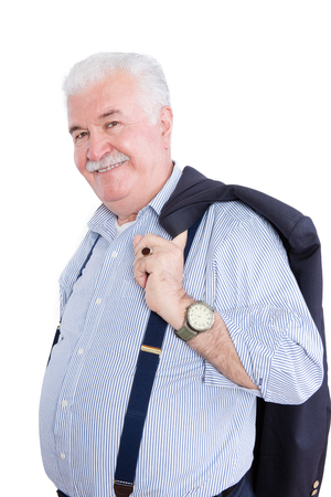 Distinguished white haired retired gentleman with his suit jacket slung over his shoulders and wearing suspenders smiling happily at the camera, on white