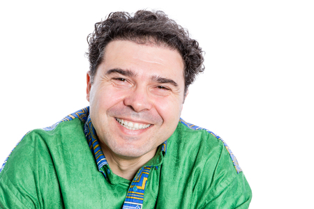 Happy handsome man with curly brown hair wearing a green afro shirt looking at the camera with a wide beaming smile of pleasure and delight, isolated on white