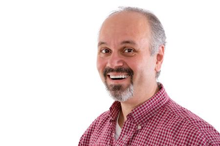 hombre rojo: Atractivo hombre de mediana edad con una perilla que llevaba una camisa a cuadros roja y una encantadora sonrisa mirando de reojo a la cámara, cabeza y los hombros aislados en blanco