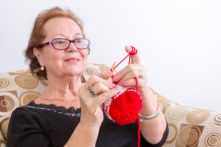 look pleased: Senior lady sitting knitting at home holding up her colorful red knitting in front of her with a pleased look of concentration, isolated on white
