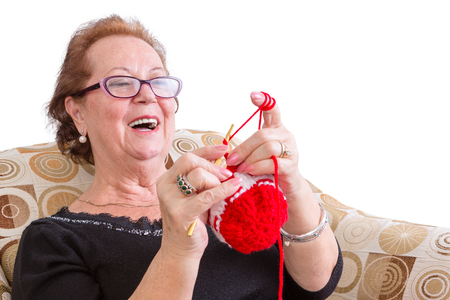 La señora mayor feliz disfrutando de una broma riendo mientras se concentra en su colorido tejer roja festiva mientras se relaja en un cómodo sillón, aislado en blanco