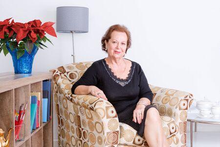 Gracieuze elegante senior vrouw ontspannen thuis in een comfortabele fauteuil zitten lachend naar de camera, feestelijke rode poinsettia bloemen in een vaas Stockfoto