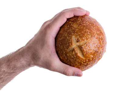 grasping: Clean male hand grasping a sourdough bun or bread roll with a crispy crust decorated with a cross isolated on white Stock Photo